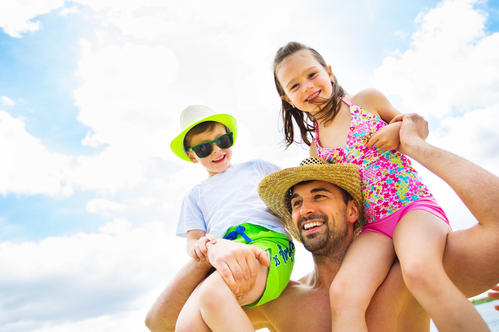 Vater und Kinder haben Spa am Strand
