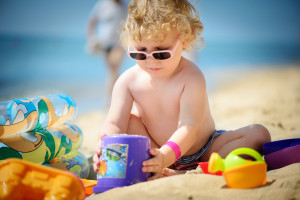 Familienferien Badeferien Mädchen spielt im Sand am Sandstrand