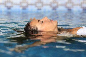 Luxusferien_Luxushotels am Meer_Badeferien_Frau entspannt im Pool