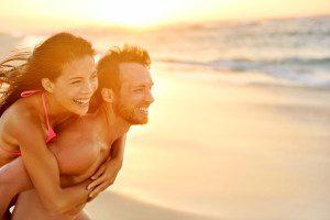 Ferien zu zweit Badeferien junges Paar am Strand im Abendlicht